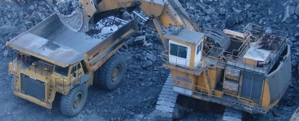 An excavator dumps raw ore into a large dumptruck